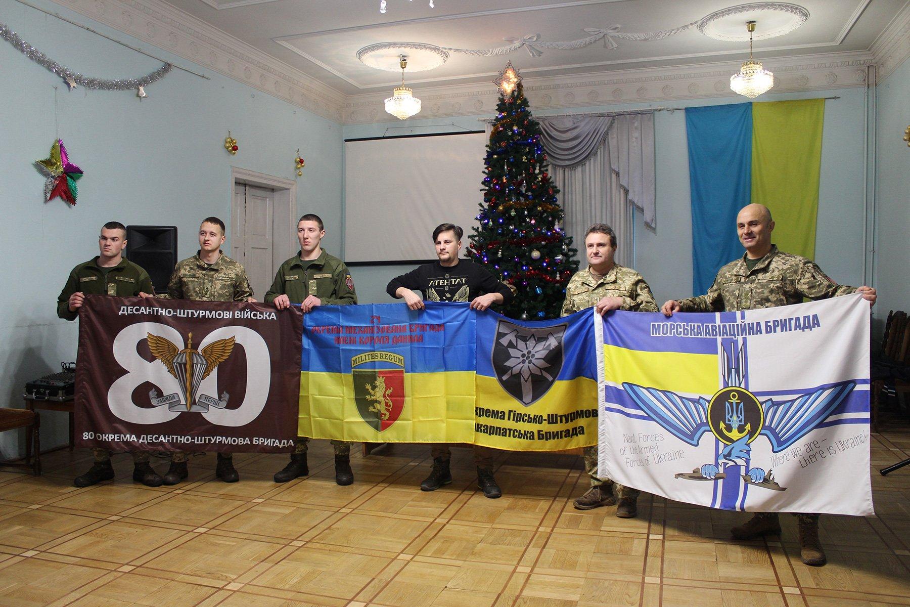 Андрій Мочурад з побратимами тримають прапори, які він доставить на станцію «Академік Вернадський»